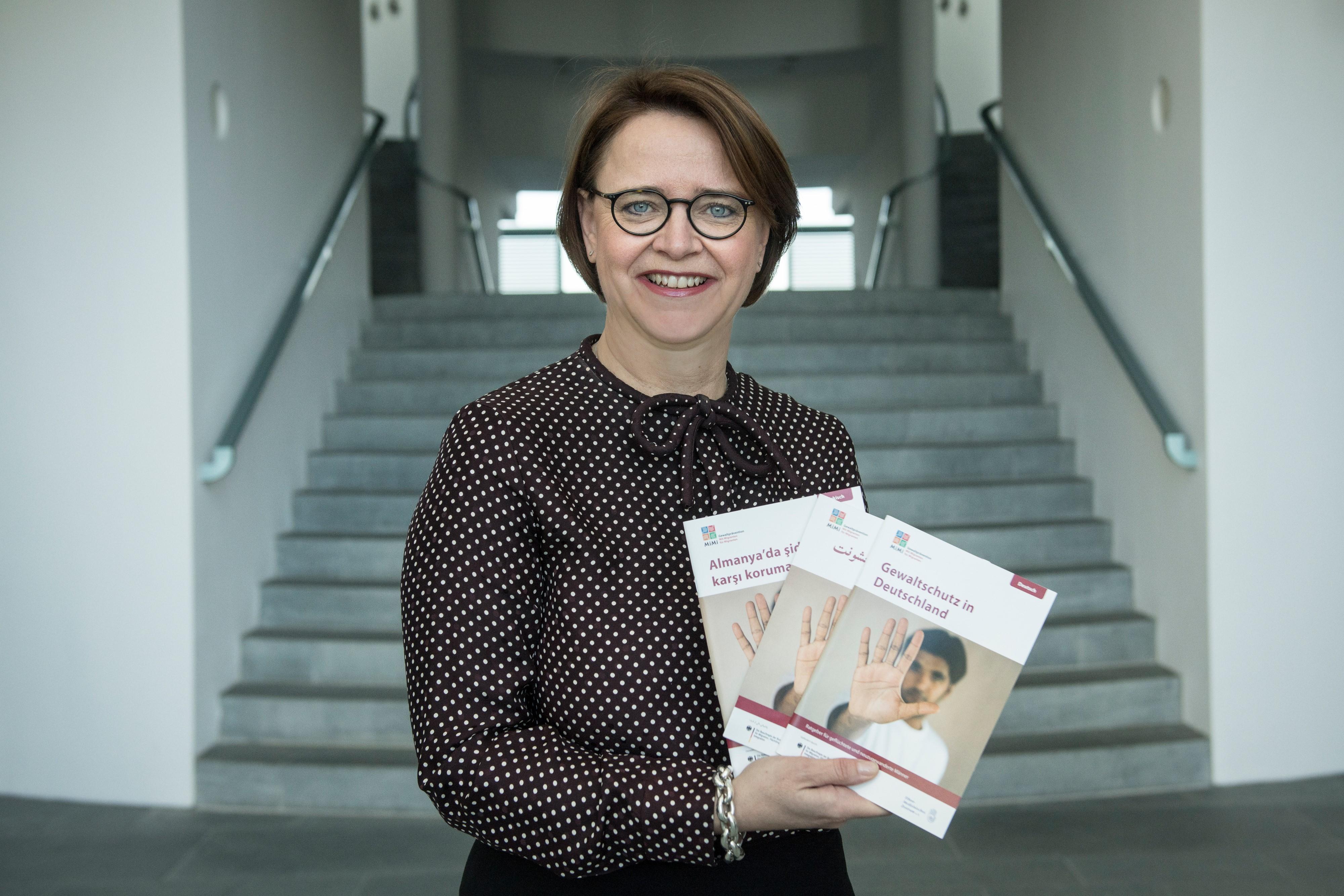 Das Bild zeigt Staatsministerin Widmann-Mauz mit dem neuen Ratgeber Gewaltschutz in Deutschland.