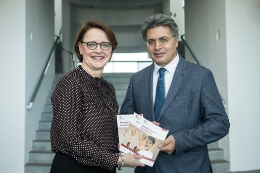 Das Bild zeigt Staatsministerin Widmann-Mauz und Professor Kizilhan bei der Übergabe des neuen Ratgebers Gewaltschutz in Deutschland.